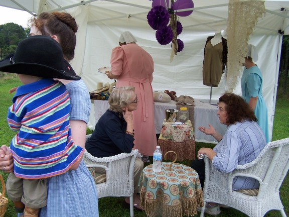 People visiting and looking at yarn in the fiber tent.